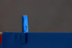 Blue shirt and blue clothespin Stock Photos