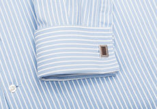 Blue shirt collar and cuff links. Sleeve of a striped blue shirt with a cuff link isolated on white background Stock Image