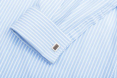 Blue shirt collar and cuff links. Sleeve of a striped blue shirt with a cuff link isolated on white background Stock Photo