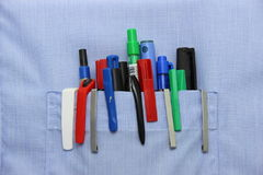 Blue shirt pocket with many different ballpoint pen Royalty Free Stock Photography
