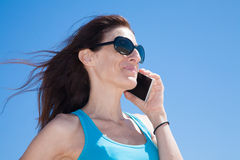 Blue shirt profile woman talking on mobile phone Stock Photography