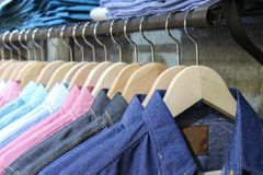 Blue shirt shop, through new clothes during shopping, Colorful man in a retail shop. Fashion and shopping business concept. jeans.  stock photo