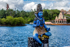Blue Shiva statue and a temple Stock Photos