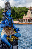 Blue Shiva statue and a temple Royalty Free Stock Photo