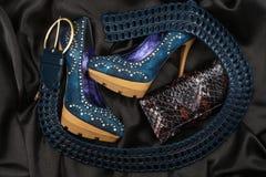 Blue shoes and belt, purse lying on black satin Stock Image