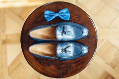 Blue shoes and bow tie on a wooden round stool. Accessory for formal dress. Symbol of elegance and fashion for men. Stock Photos