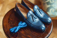 Blue shoes and bow tie on a wooden round stool. Accessory for formal dress. Symbol of elegance and fashion for men. Stock Images