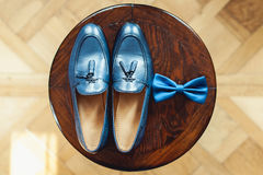 Blue shoes and bow tie on a wooden round stool. Accessory for formal dress. Symbol of elegance and fashion for men. Royalty Free Stock Image