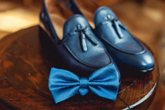 Blue shoes and bow tie on a wooden round stool. Accessory for formal dress. Symbol of elegance and fashion for men. Royalty Free Stock Photography