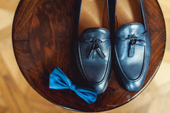 Blue shoes and bow tie on a wooden round stool. Accessory for formal dress. Symbol of elegance and fashion for men. Stock Photo