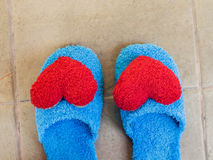 Blue shoes in house with red heart on floor Royalty Free Stock Photography