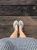 Blue Shoes Isolated on Wood Floor for Top View. Woman Wearing Blue Flip Flop and Blue Scot Dress on The Wooden Floor Background. Great For Any Use Royalty Free Stock Photo
