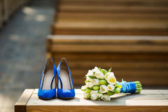 Blue shoes and white tulips Stock Photos
