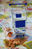 Blue shopping cart and coin stack. Blue shopping cart and a small glass bottle with coins on background made of euro banknotes and coins Stock Photos