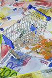 Blue shopping cart on money. Blue small shopping cart on a background made of Euro banknotes and coins Stock Images