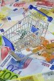 Blue shopping cart on money Stock Images