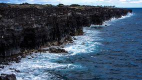 Blue Shores of Hawaii. Snapshot of Hawaii`s coastline. This rocky shore beautifully reflects the deep blue water below Stock Photo