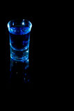 Blue Shot. Style drink on black background and glass surface royalty free stock images