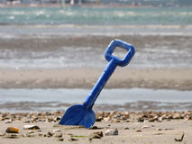 Blue shovel in the sea sand Royalty Free Stock Image