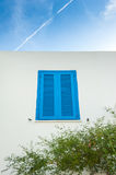 Blue shutter window and sky with contrail Stock Photo