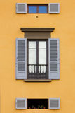 Blue shutter window on yellow wall. Two small windows and one big with blue shutters on a yellow wall Royalty Free Stock Image