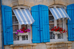 Blue Shutter Windows with Flower Pots. Bright blue awnings and shutters are accented by  fuchsia and red flowers on the window sills in Arles, France Stock Photography