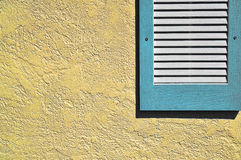 Blue shutter on yellow exterior wall Stock Photo