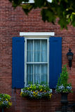 Blue shuttered window with flower box. Blue shuttered window on a brick building with a flower box and accent plants Stock Photos