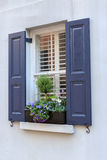 Blue Shuttered Window and Window Box Flowers Royalty Free Stock Photos