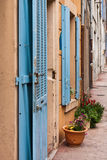 Blue shutters. Houses with blue shutters in a row in a small village in Provence in France stock images