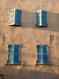 Blue Shutters. Four windows with blue shutters on a wall Royalty Free Stock Photo