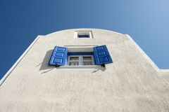 Blue shutters, blue sky, white wall. Blue shutters open on a window in the end wall of a house on Santorini island with blue skies royalty free stock image