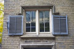 Blue shutters outside a old window in Toronto, Canada royalty free stock photo