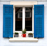 Blue Shutters and Red Pot. A window with bright blue shutters reflects an older house.  A plant in a bright red pot is on the windowsill Stock Photos