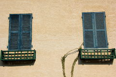 Blue Shutters. Two windows with blue, closed shutters Stock Image