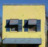 Blue shutters on yellow building Royalty Free Stock Images