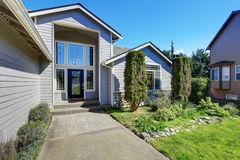 Blue siding house with elegant front door and side windows Stock Image
