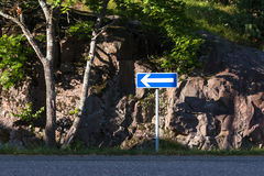 Blue sign with left arrow on the side of the road. stock photos