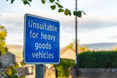 A blue sign that says `Unsuitable for heavy goods vehicles` stock photos