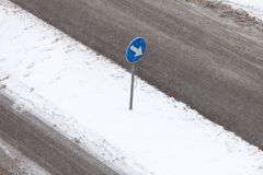 Blue sign with white arrow on road during winter royalty free stock photography