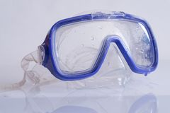 Blue silicone swimming mask on white table with reflection. Diving Snorkel blue silicone swimming mask on white table with reflection stock photo