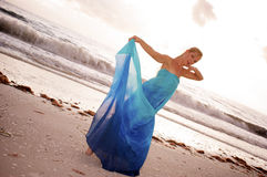 Blue silk dancer. A beautiful dancer wrapped in blue silk is on pointe at the beach with waves crashing in the background with her looking at you the viewer with Stock Image