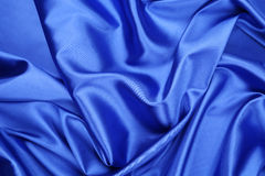 Blue silk drapery. Located as a whole background Royalty Free Stock Photography