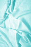 Blue silk fabric. Abstract background, blue silk fabric with waves. Shallow DOF Stock Images
