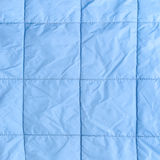 Blue silk quilted fabric as a background. Closeup Royalty Free Stock Images