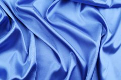 Blue silk with some soft folds and highlights. Whole background stock images