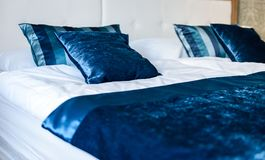 Blue silky hotel room bedding pillows and sheets on bed. Bed decoration with two stacked pillows on prepared fresh double bed. Vacation concept with hotel Stock Images