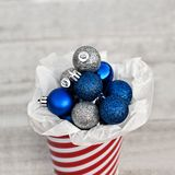Blue and Silver Balls Collected in Striped Bucket for the Christ. Mas Decor, Winter Holiday Concept, USA royalty free stock image