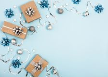 Christmas frame composition with silver decor and gifts on pastel blue background. Flat lay. Copy space royalty free stock photo