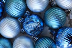 Blue and silver Christmas balls close together. Christmas balls close together with some silver balls as well. The balls all have stripes on them. Beautiful Royalty Free Stock Photography